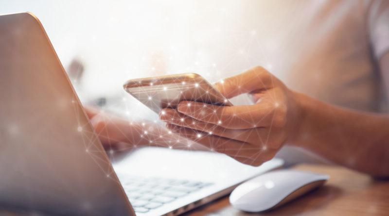 Frau Hand mit Handy und Laptop-Daten-Synchronisation – Stockfoto
